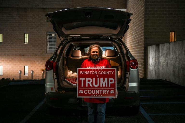 Ronnie Mobley poses with a 'Trump Country' sign after a Republican Party meeting in the Winston County courthouse in Double Springs, Alabama on October 12, 2020