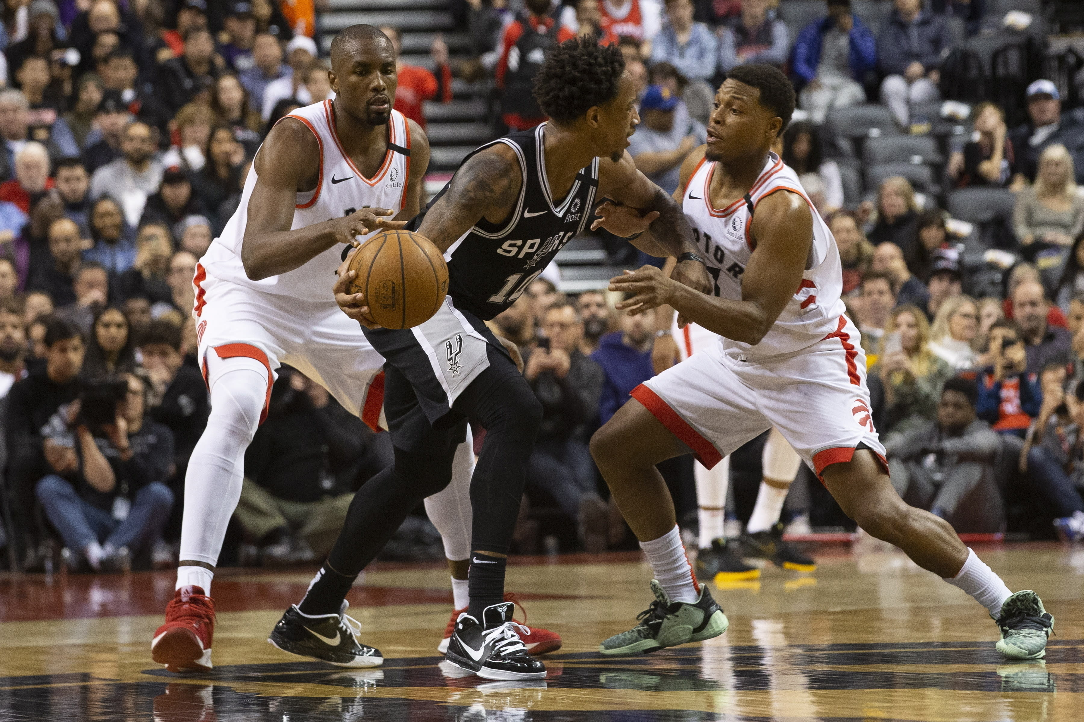 DeMar DeRozan, de los Spurs de San Antonio, conduce el balón entre Kyle Lowry (derecha) y Serge Ibaka, de los Raptors de Toronto, durante el partido del domingo 12 de enero de 2020 (Chris Young/The Canadian Press via AP)