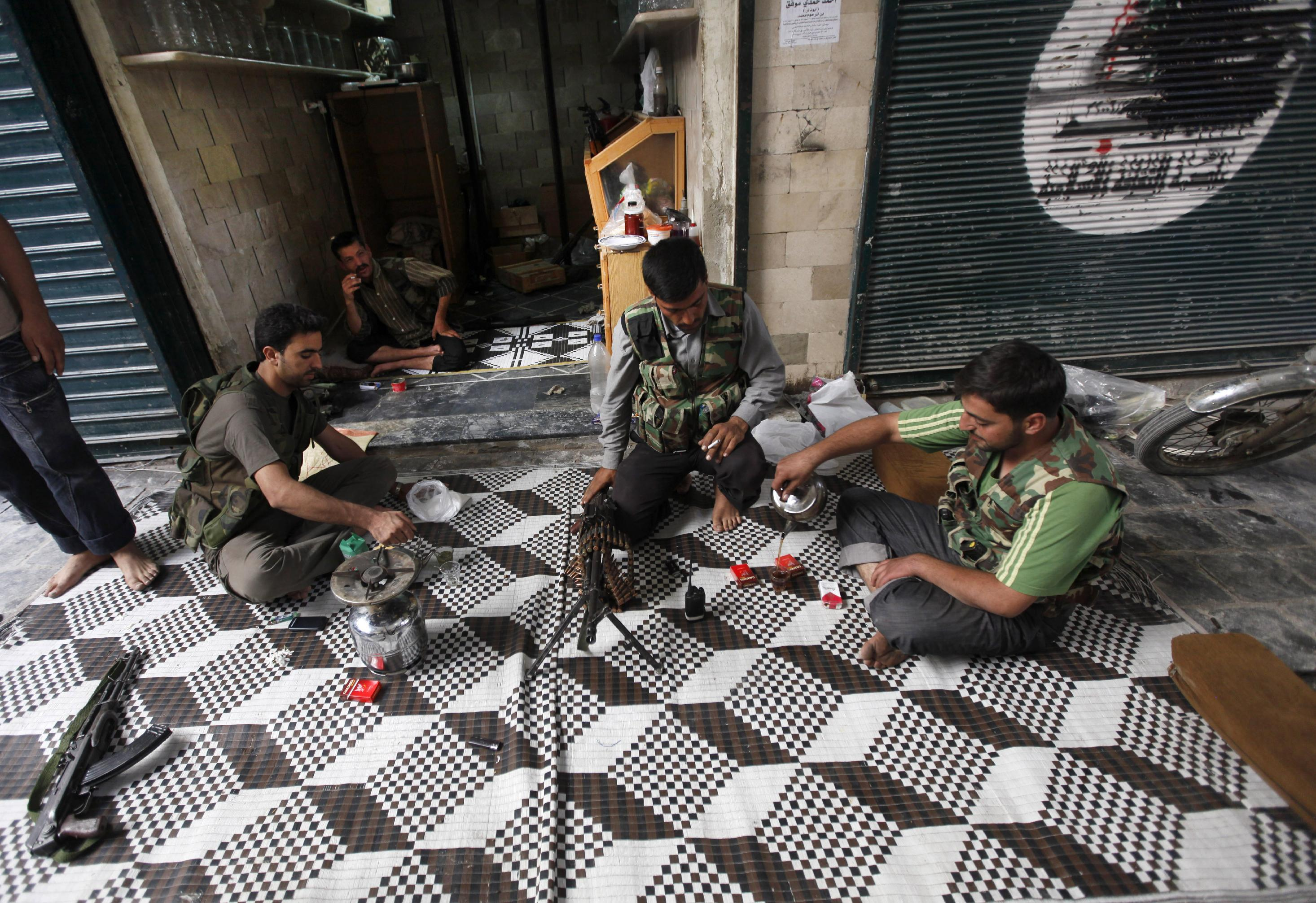 """In this picture taken on Monday September 24, 2012, Free Syrian Army fighters drink tea next to closed shops, at the souk of the old city of Aleppo city, Syria. Fires sparked by clashes between government troops and rebels raged through the medieval marketplace of Aleppo on Saturday, destroying hundreds of shops lining the vaulted passageways where foods, fabrics, perfumes and spices have been sold for centuries, activists said. Arabic writing on the closed shop at right reads:""""Aleppo.""""(AP Photo/Hussein Malla)"""