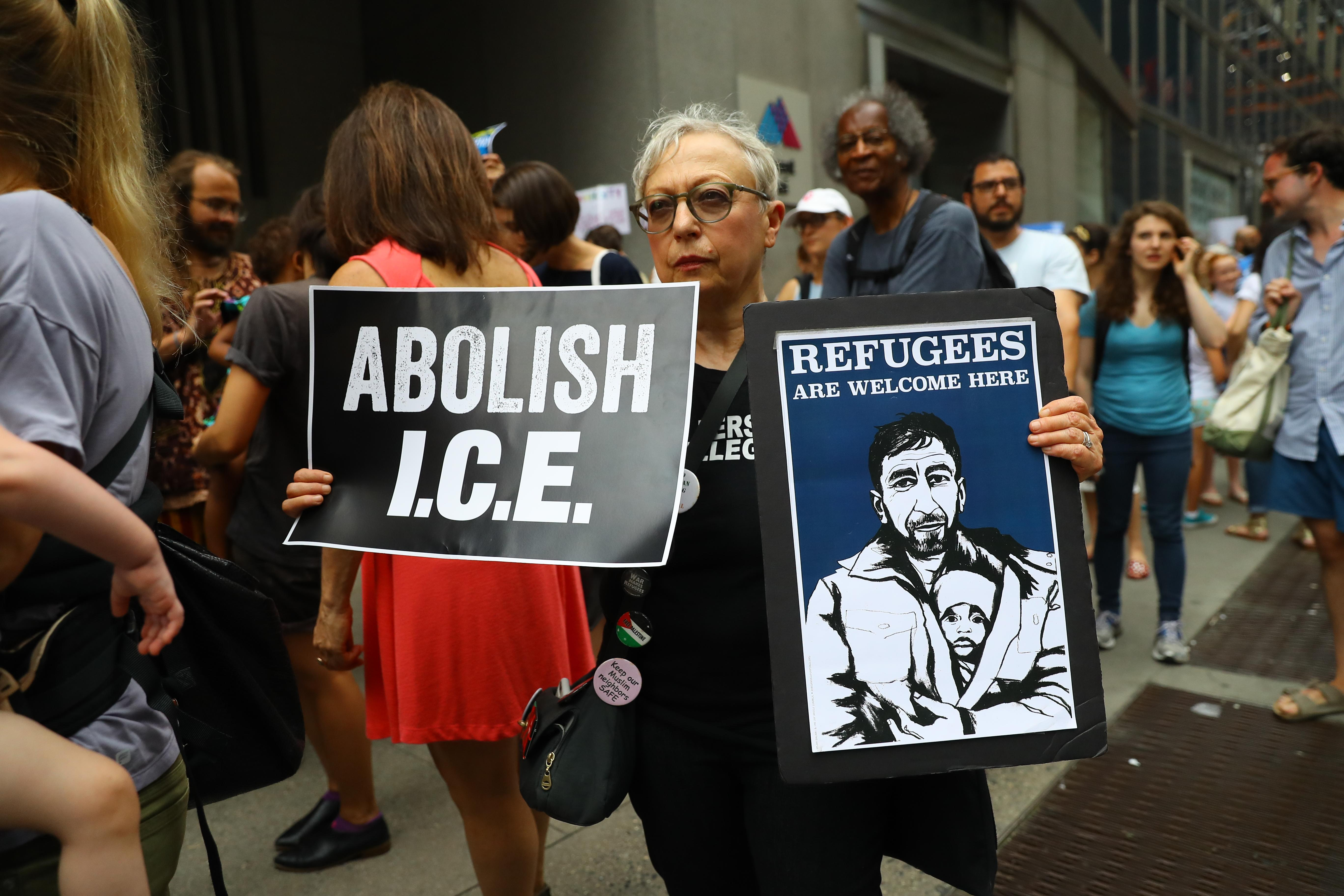 """<p>Protester Jenny Hines of Manhattan holds up signs that read to """"Abolish I.C.E."""" and """"Refugees are welcome here"""" on 42nd Street in New York City on June 20, 2018. (Photo: Gordon Donovan/Yahoo News) </p>"""