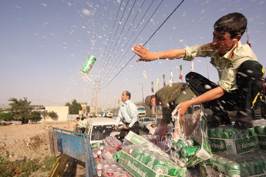 Iranian police dump confiscated beer cans in Tehran in 2009. The possession, production and consumption of alcohol is strictly forbidden in the Islamic Republic and police often raid smugglers and illegal parties