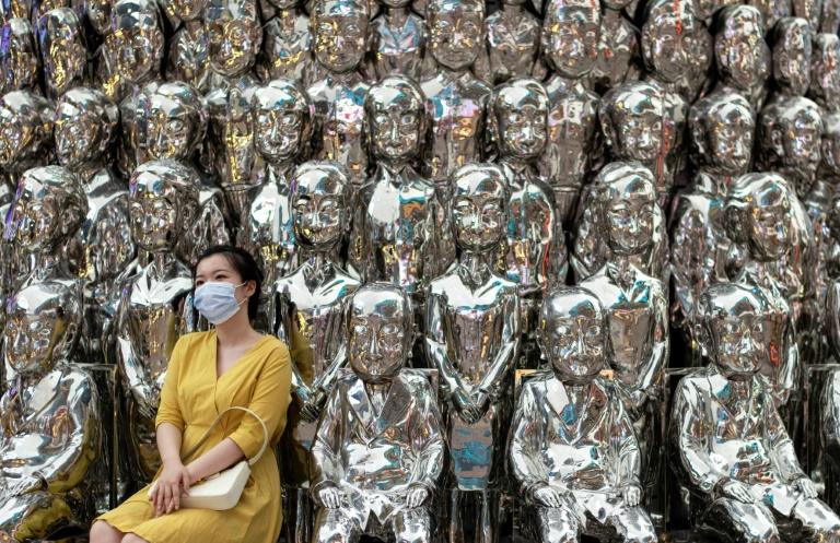 Face masks, such as the one this woman is wearing as she poses for a photo at a shopping center in Beijing on August 23, 2020, were not yet in common use when the bus ride in Ningbo occurred