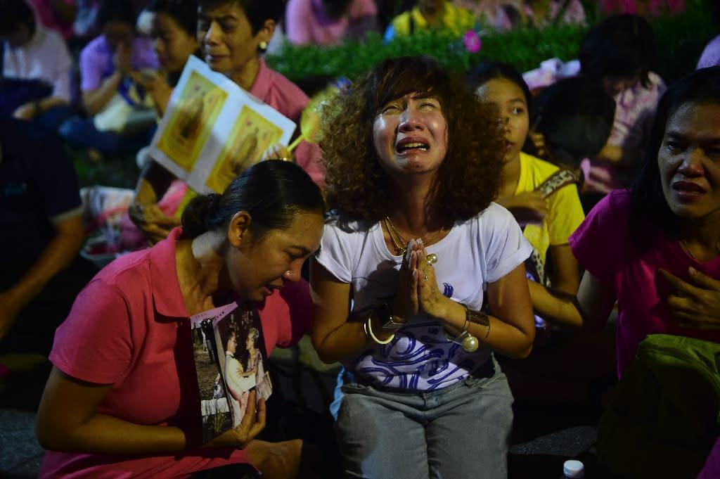 Thais react to the death of King Bhumibol Adulyadej at Siriraj Hospital in Bangkok on October 13, 2016 (AFP Photo/Munir Uz Zaman)