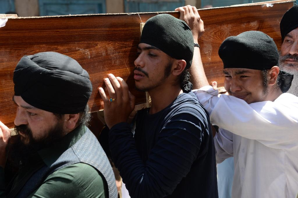 "Scores of mourners shouted ""death to Ashraf Ghani"" and ""death to the government"" as they placed coffins in ambulances that would take them to a temple for funeral ceremonies (AFP Photo/NOORULLAH SHIRZADA)"
