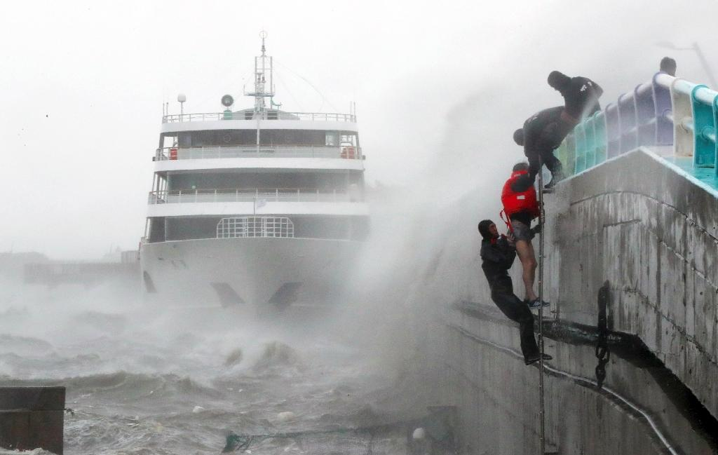 Coast guards rescue crew members of a stranded passenger ship in the aftermath of Typhoon Chaba in Yeosu on October 5, 2016 (AFP Photo/)