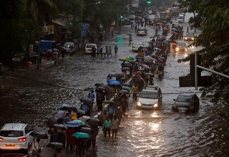 Commuters walk through water-logged roads after rains in Mumbai, India, August 29, 2017. REUTERS/Shailesh Andrade