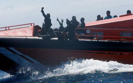 Migrants wave on a rescue boat as they are carried towards the port of Tarifa