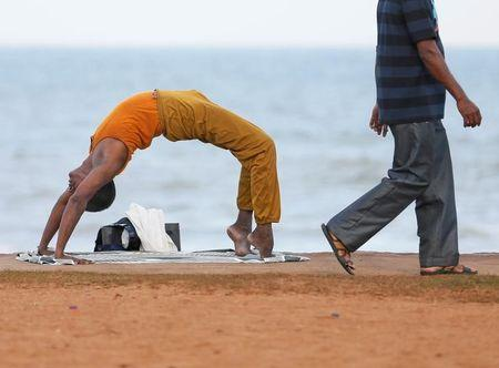 A man performs yoga as another man walks past him at Galle Face Green in Colombo