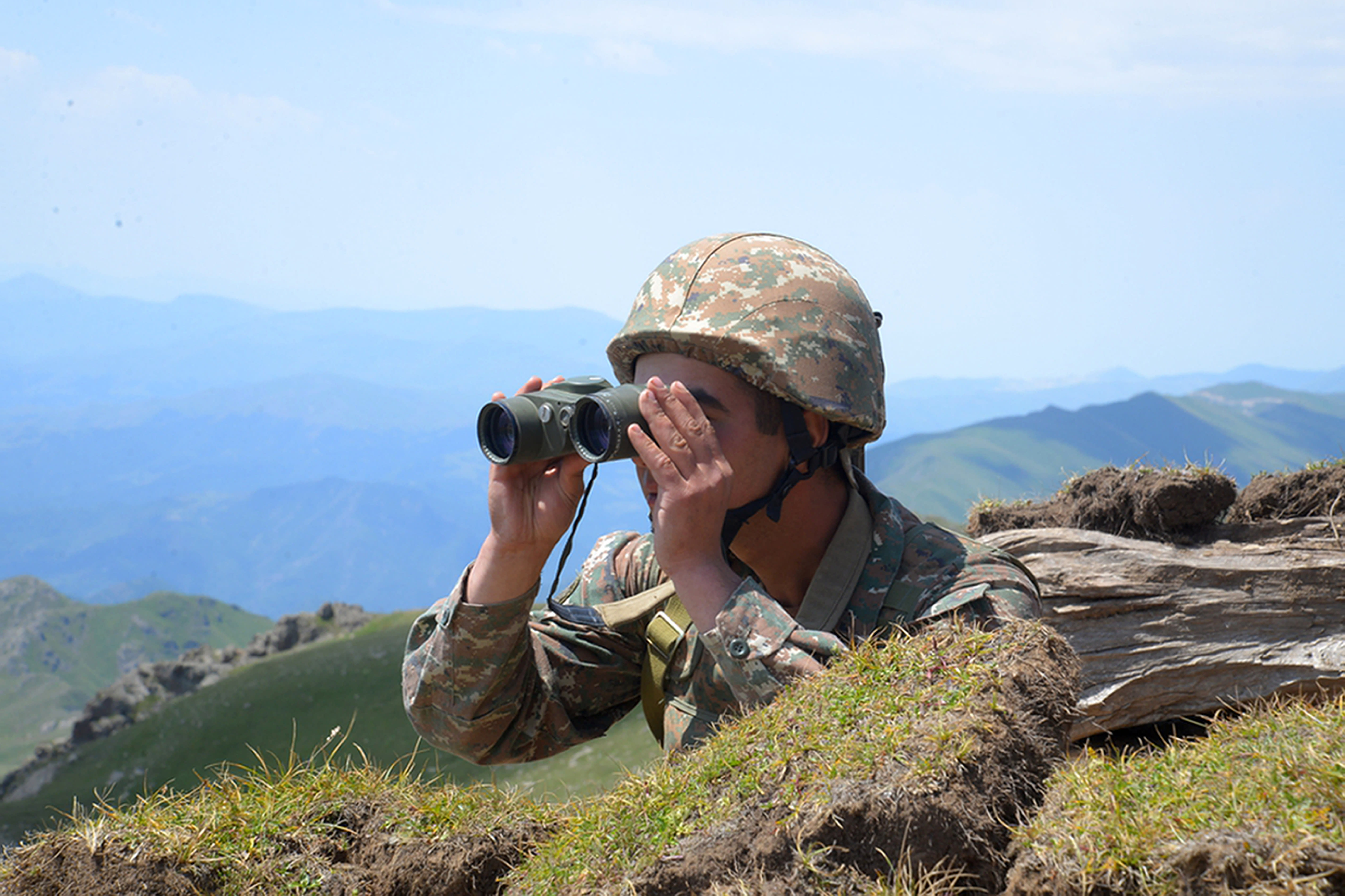 An Armenian soldier looks through a binocular at his position on the front line in Tavush region, Armenia, Tuesday, July 14, 2020. Skirmishes on the volatile Armenia-Azerbaijan border escalated Tuesday, marking the most serious outbreak of hostilities between the neighbors since the fighting in 2016. (Armenian Defense Ministry Press Service/PanPhoto via AP)