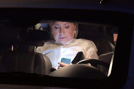 Democratic nominee Hillary Clinton looks at her mobile phone as she leaves her house to attend Congressional Black Caucus Foundation's Phoenix Awards Dinner at the Washington convention center in Washington
