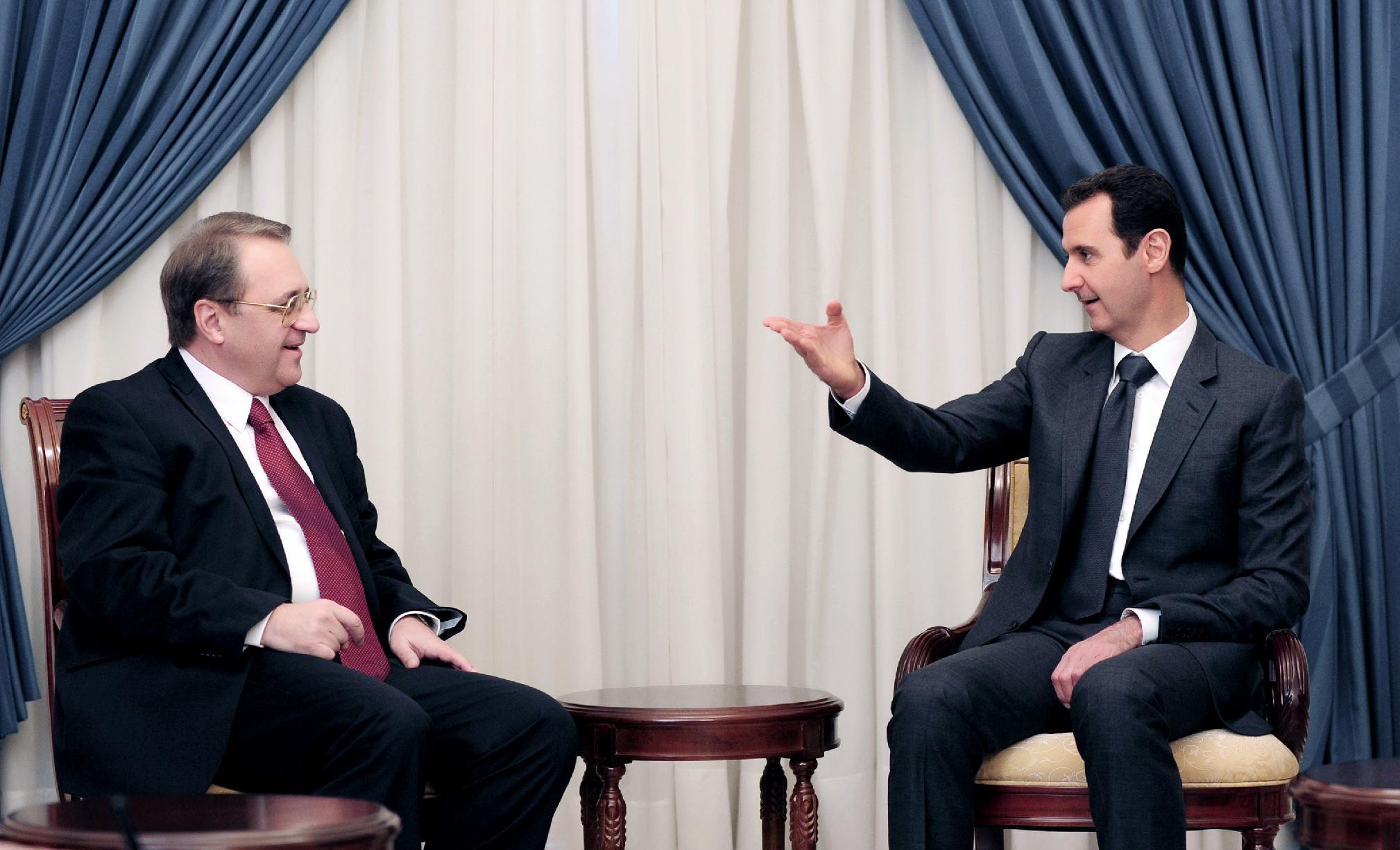 A picture released by the Syrian Arab News Agency on December 10, 2014 shows President Bashar al-Assad (R) meeting with Russian Deputy Foreign Minister Mikhail Bogdanov in Damascus