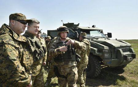 Ukraine's President Petro Poroshenko (2nd L) listens to explanations as he inspects a military drill, with the National Security and Defence Council Oleksandr Turchynov (L) seen nearby, at a training ground near the city of Mykolaiv April 25, 2015. REUTERS/Mykola Lazarenko/Ukrainian Presidential Press Service/Handout via Reuters ATTENTION EDITORS - THIS PICTURE WAS PROVIDED BY A THIRD PARTY. REUTERS IS UNABLE TO INDEPENDENTLY VERIFY THE AUTHENTICITY, CONTENT, LOCATION OR DATE OF THIS IMAGE. FOR EDITORIAL USE ONLY. NOT FOR SALE FOR MARKETING OR ADVERTISING CAMPAIGNS. THIS PICTURE IS DISTRIBUTED EXACTLY AS RECEIVED BY REUTERS, AS A SERVICE TO CLIENTS