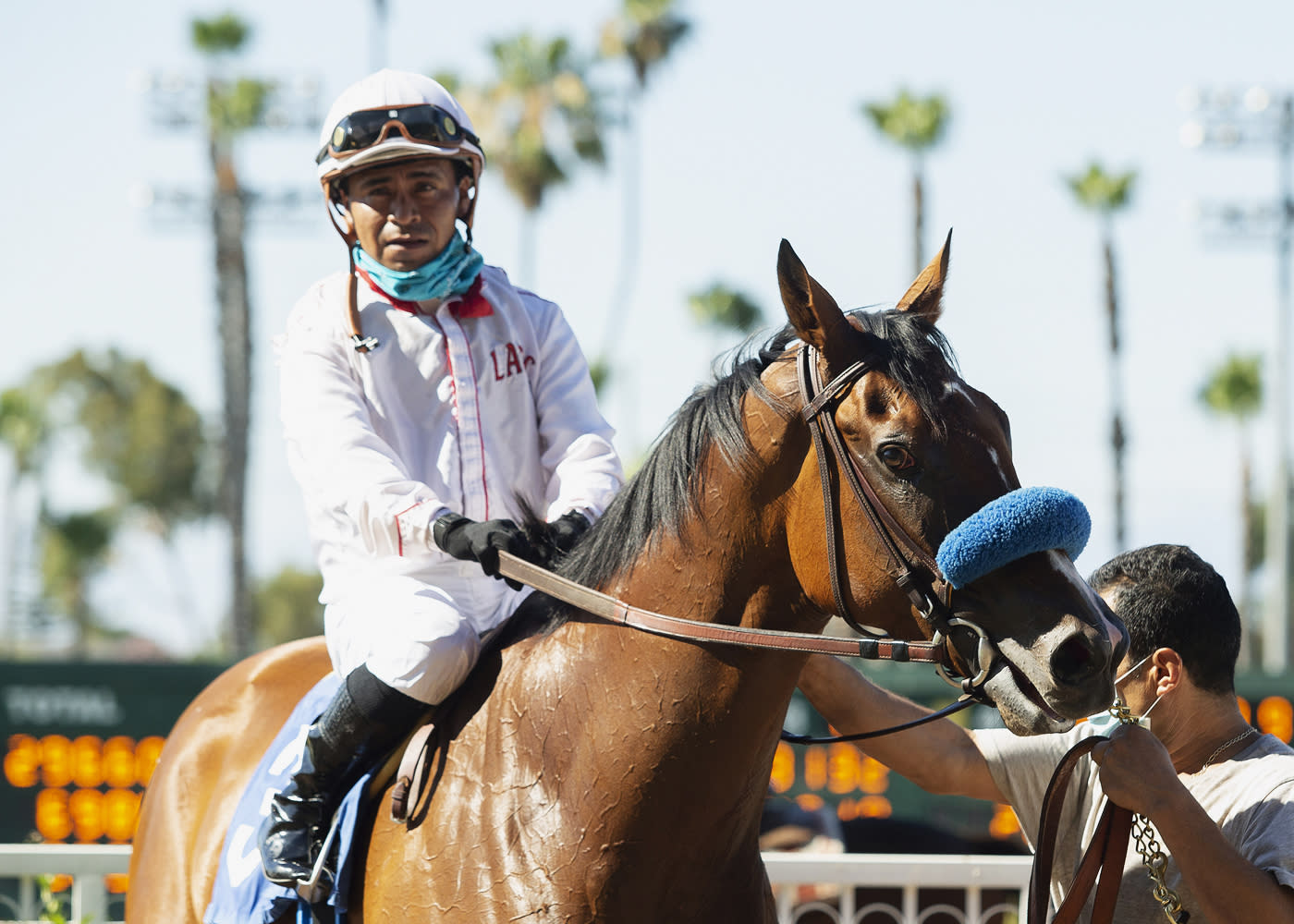 In this image provided by Benoit Photo, Jockey Martin Garcia guides Sneaking Out to the winner's circle after their victory in the Martin Garcia win the Grade II, $200,000 Great Lady M Stakes, Saturday, July 4, 2020 at Los Alamitos Race Course, Cypress Calif. (Benoit Photo via AP)
