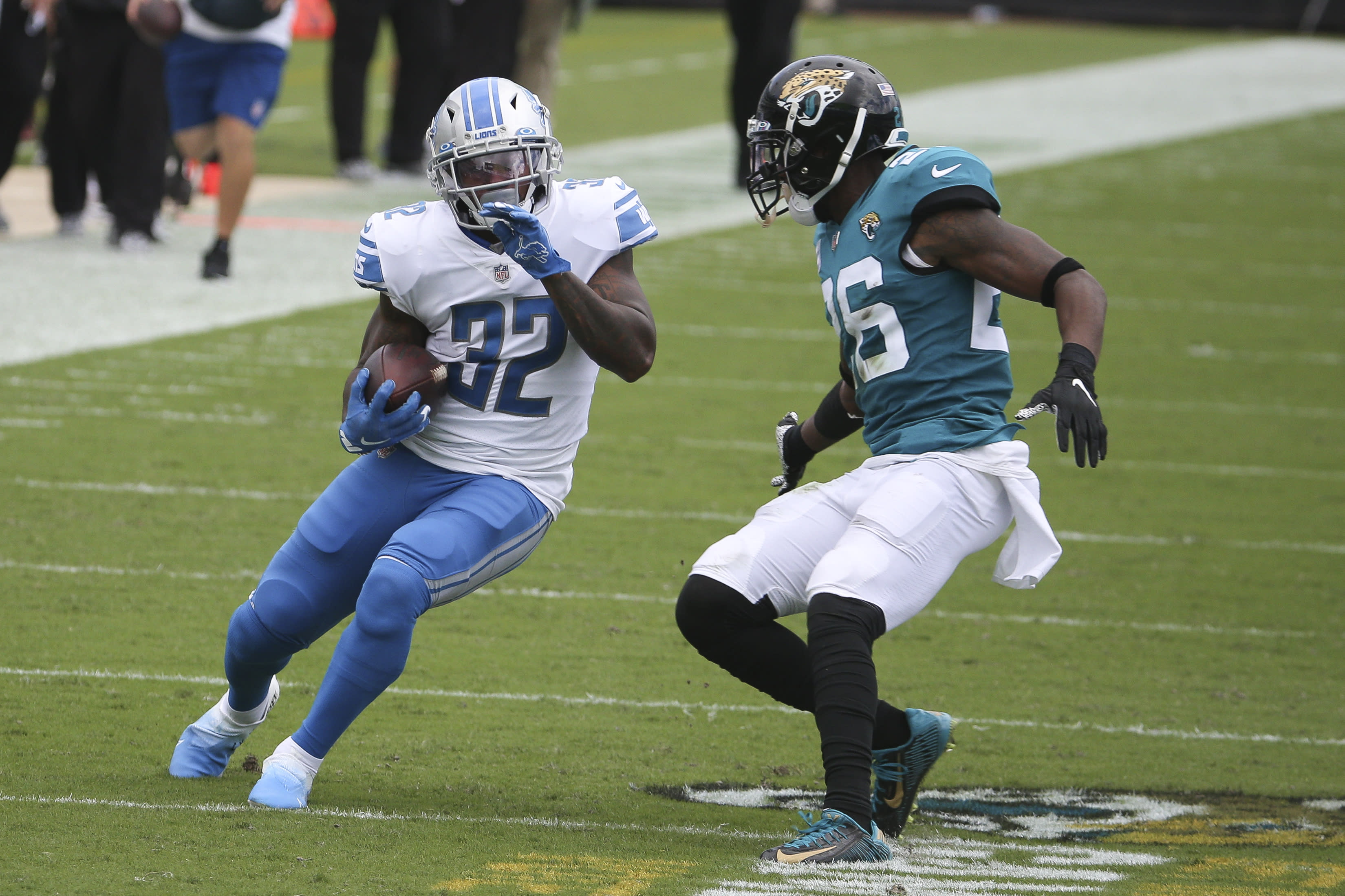 Detroit Lions running back D'Andre Swift (32) tries to avoid a tackle by Jacksonville Jaguars safety Jarrod Wilson, right, during the first half of an NFL football game, Sunday, Oct. 18, 2020, in Jacksonville, Fla. (AP Photo/Stephen B. Morton)