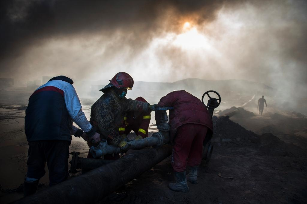 Workers tasked with putting out the fire in an oil well assemble a water pipeline in the town of Qayyarah, some 70 km south of Mosul on November 20, 2016 (AFP Photo/Odd Andersen)