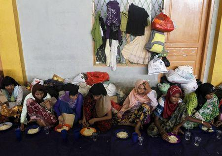 Migrants, believed to be Rohingya, take their breakfast inside a shelter after being rescued from boats at Lhoksukon, in Indonesia's Aceh Province May 12, 2015. REUTERS/Roni Bintang