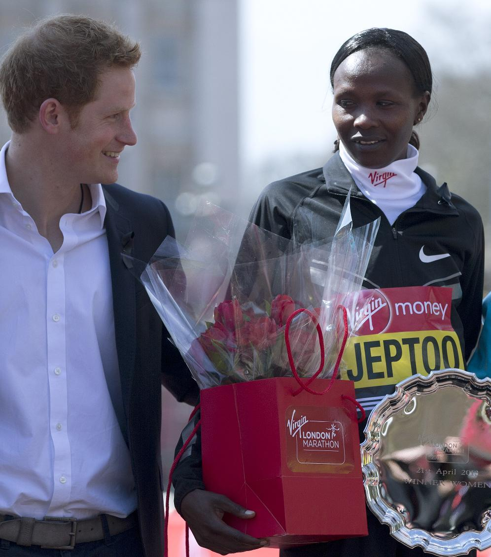 Priscah Jeptoo of Kenya, right, winner of the women's marathon with Britain's Prince Harry, left, pose on the podium after the medal presentations for the London Marathon in the Mall, Sunday, April 21, 2013. A defiant, festive mood prevailed Sunday as the London Marathon began on a glorious spring day despite concerns raised by the bomb attacks on the Boston Marathon six days ago, as thousands of runners offered tributes to those killed and injured in Boston, with a moment of silence before the race, and many wore black ribbons as a sign of solidarity.(AP Photo/Alastair Grant)