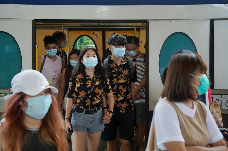 People walk out of a train at a subway station near the Hong Kong Disneyland Resort in Hong Kong