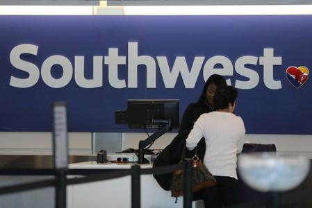 A traveler checks her baggage at the Southwest Airlines terminal at LAX airport in Los Angeles