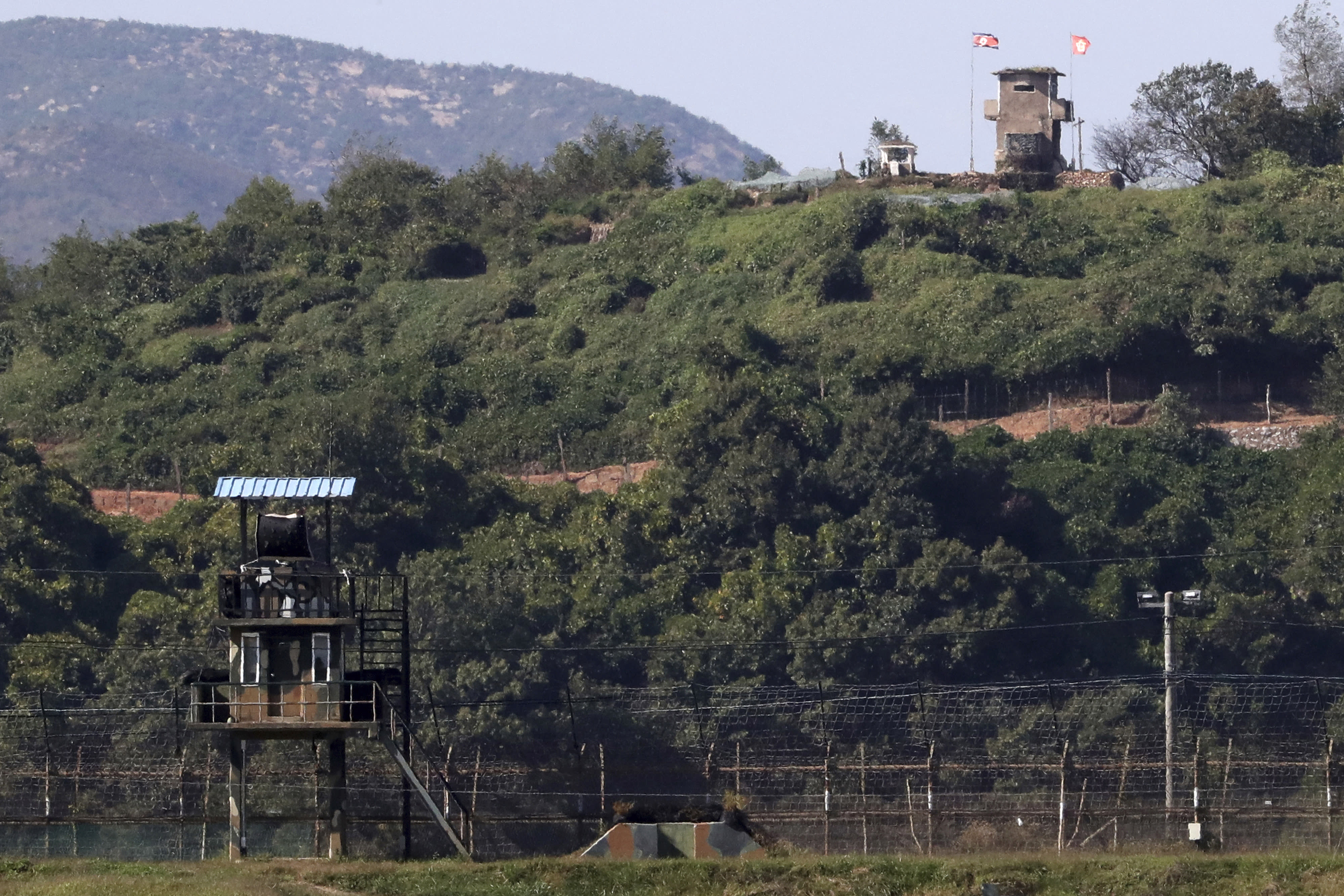 In this on Sunday, Sept. 30, 2018 photo, military guard posts of North Korea, right top, and South Korea, left bottom, are seen in Paju, at the border with North Korea, South Korea. Seoul on Monday, Oct. 1, 2018, says South Korea has begun clearing mines from two sites inside the heavily fortified border with North Korea under a package of tension-reduction deal between the rivals. (Kim Do-hoon/Yonhap via AP)