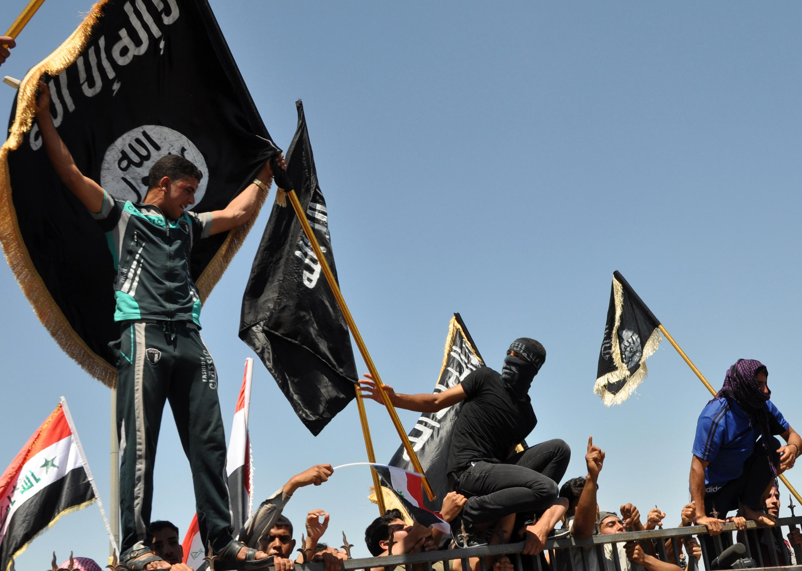 FILE - Masked Sunni protesters wave Islamist flags while others chant slogans at an anti-government rally in Fallujah, Iraq, Friday, April 26, 2013. The leader of al-Qaida's Iraq arm, Abu Bakr al-Baghdadi, defiantly rejected an order from the terror network's global command to scrap a merger with the organization's Syria affiliate, according to a message purporting to be from Al-Baghdadi that was posted online Saturday, June 15, 2013. (AP Photo/Bilal Fawzi, File)