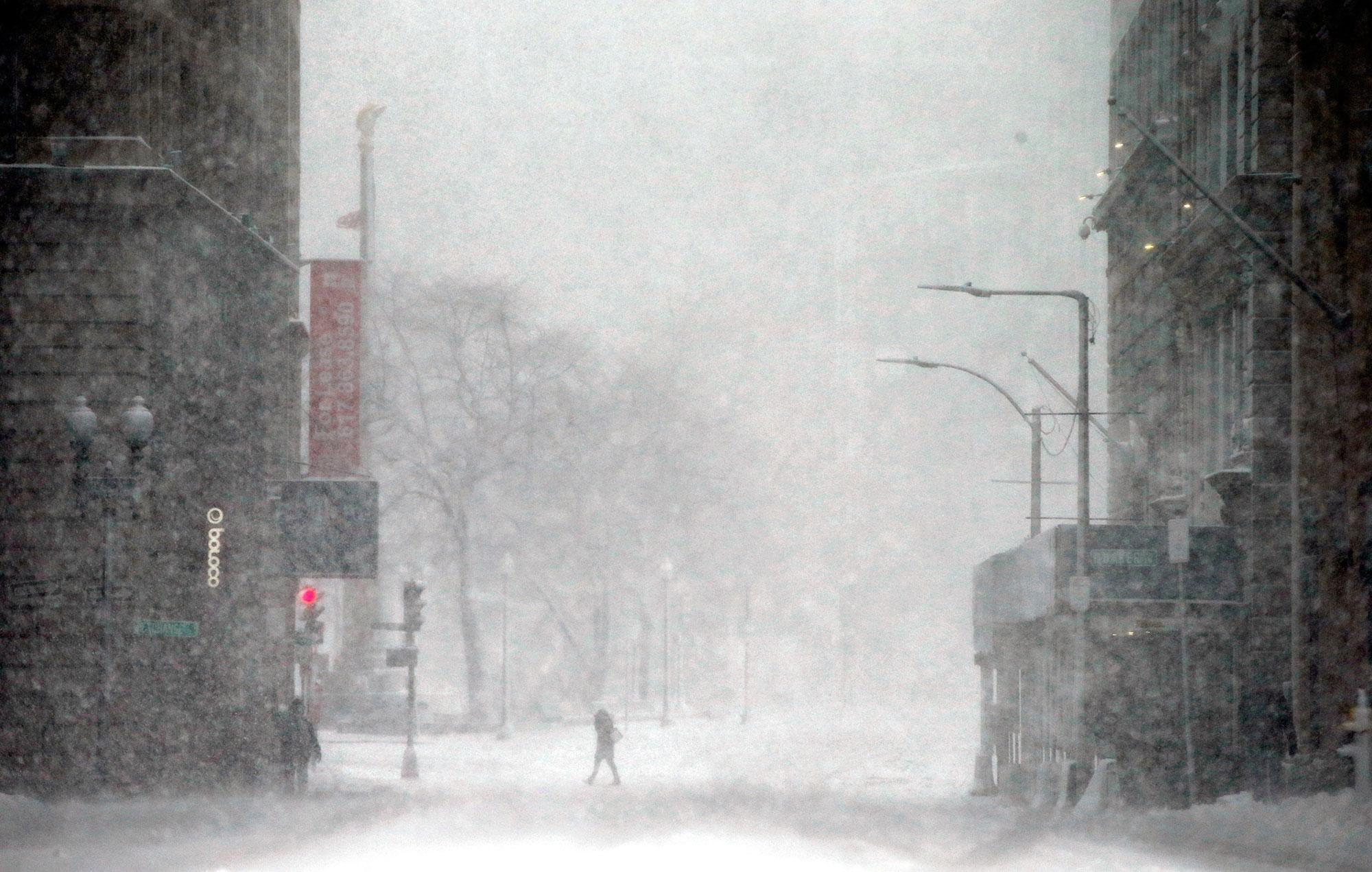 <p>A person crosses a street in blowing snow during a winter storm Tuesday, March 14, 2017, in Boston. (AP Photo/Michael Dwyer) </p>