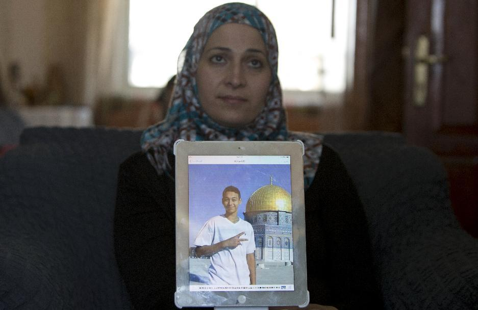 The mother of Tariq Abu Khdeir (portrait), shows a picture of her son from before he was beaten by Israeli border police in East Jerusalem on July 5, 2014