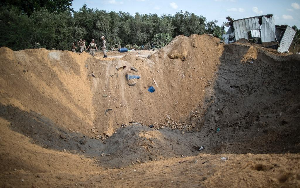 Palestinian militants of the Islamic Jihad movement inspect a crater on August 22, 2016 in the northern Gaza Strip, following an Israeli airstrike the day before (AFP Photo/Mahmud Hams)