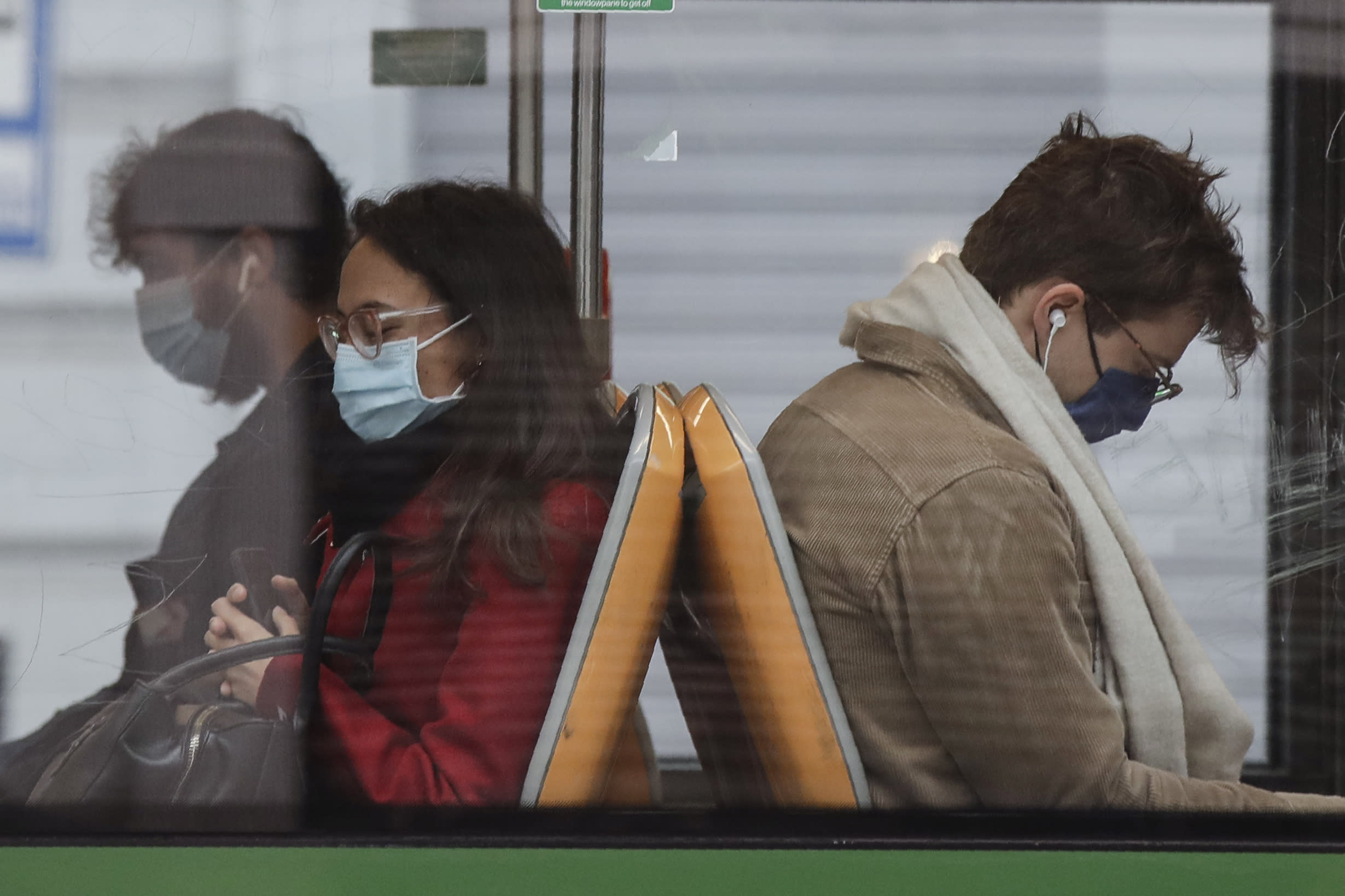 People wearing face masks to prevent the spread of COVID-19 sit on a bus, in Milan, Italy, Wednesday, Oct. 14, 2020. Italian Premier Giuseppe Conte says the aim of Italy's new anti-virus restrictions limiting nightlife and socializing is to head off another generalized lockdown. (AP Photo/Luca Bruno)