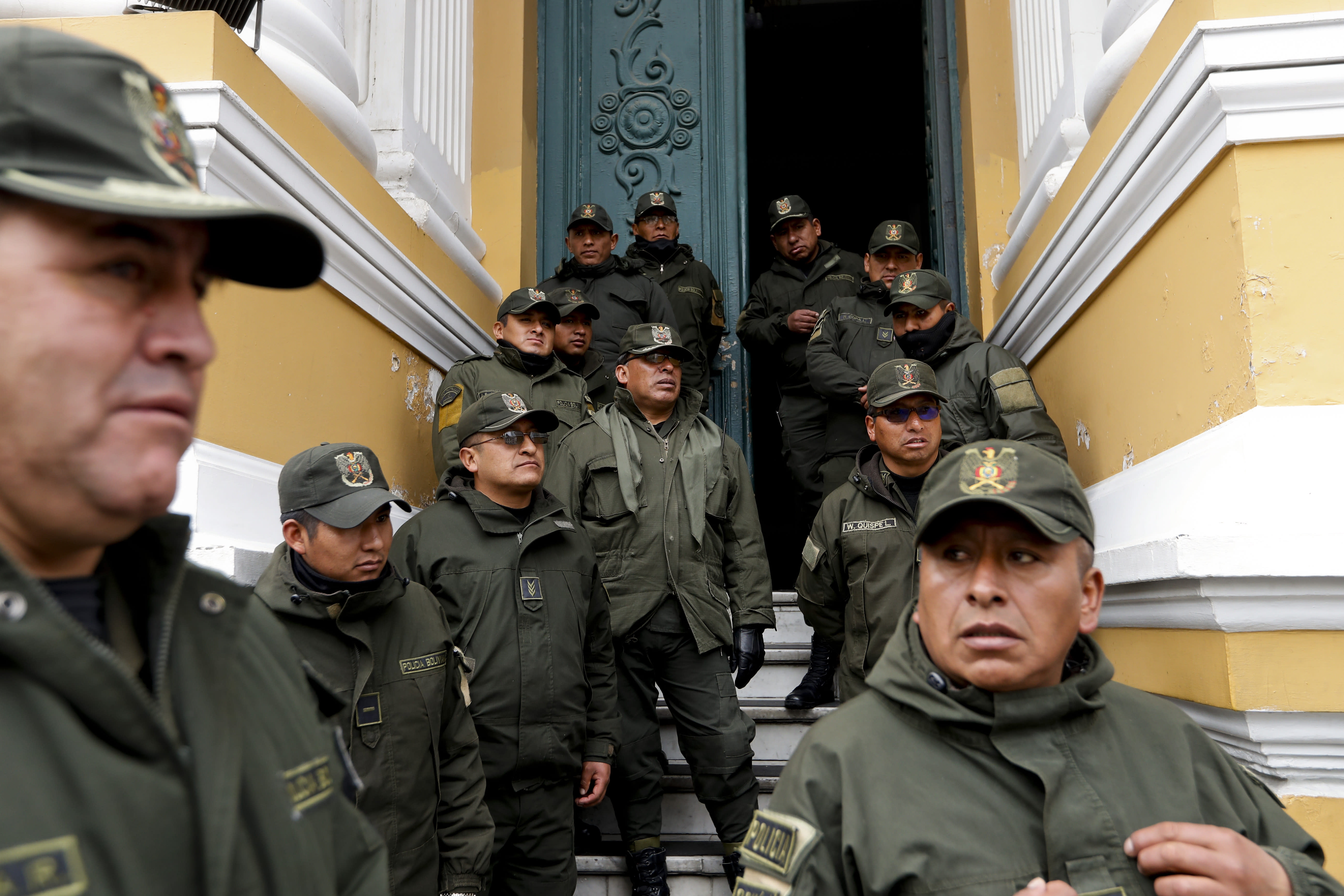 Police guard Congress in La Paz, Bolivia, Monday, Nov. 11, 2019. Bolivian President Evo Morales' Nov. 10 resignation, under mounting pressure from the military and the public after his re-election victory triggered weeks of fraud allegations and deadly demonstrations, leaves a power vacuum and a country torn by protests against and for his government. (AP Photo/Natacha Pisarenko)
