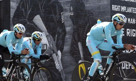 The Astana cycling team pass a loyalist paramilitary mural painted on a wall in east Belfast as they make their way around the route of the Giro d'Italia team time trial