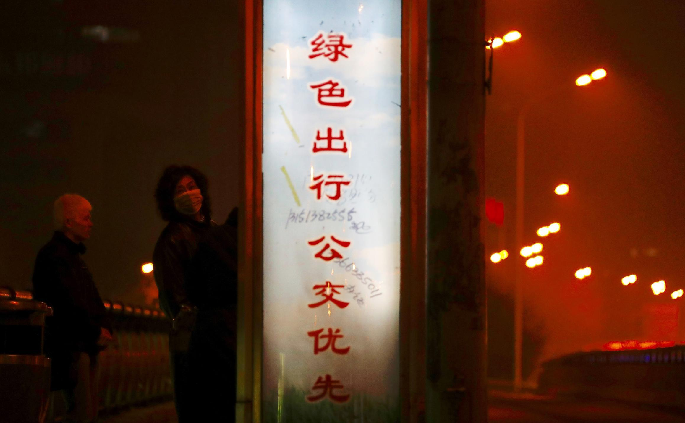 """In this Monday, Jan. 2, 2017 photo, a pedestrian wearing a mask looks back while passing by a slogan that reads: """"When you want to go out, please take a public bus"""" in Beijing. Beijing and other cities across northern and central China were shrouded in thick smog on Monday, prompting authorities to delay dozens of flights and close highways. (AP Photo/Andy Wong, File)"""