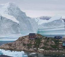 Massive 11-million-ton iceberg towers over little village in Greenland