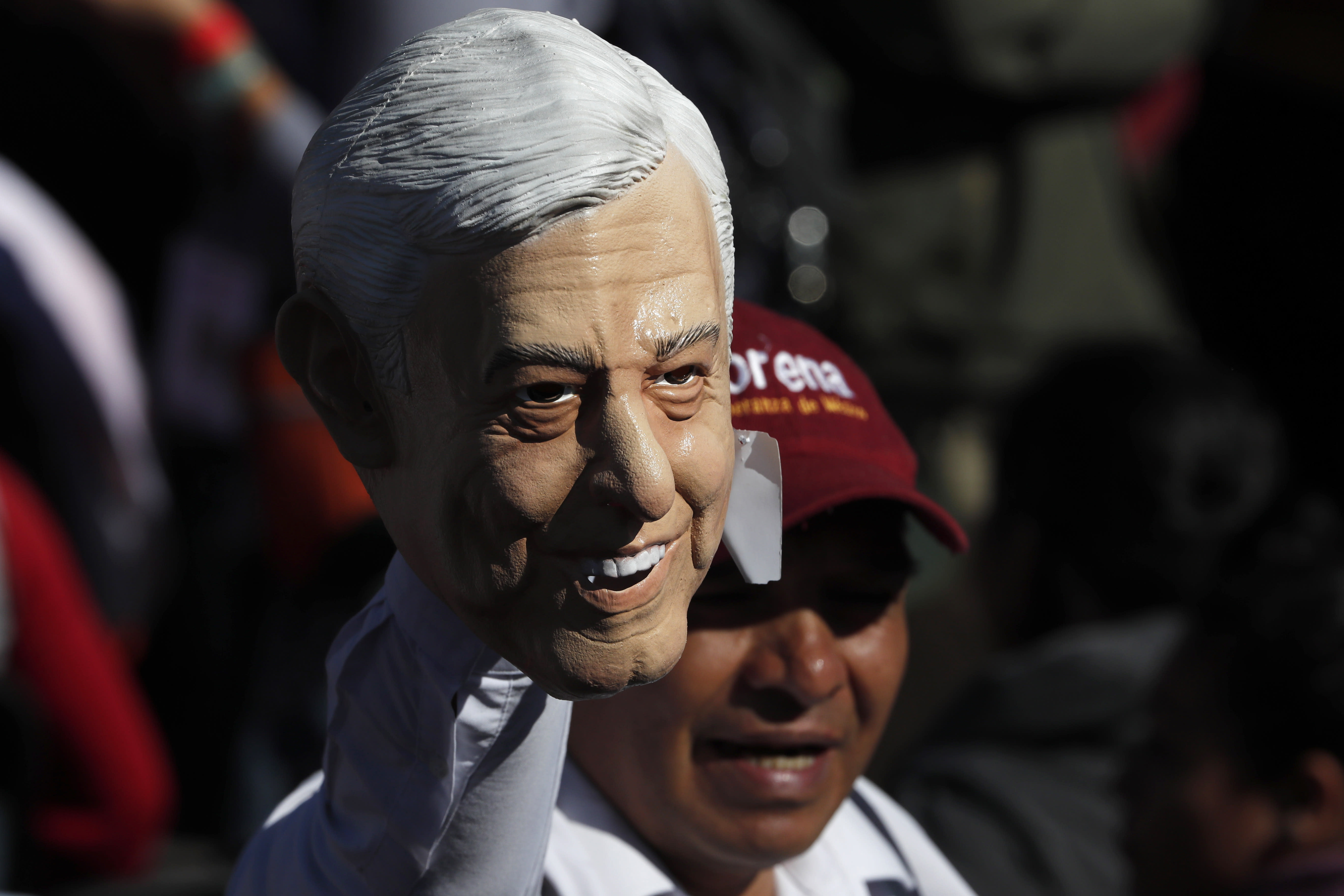 A supporter of Mexico's President Andres Manuel Lopez Obrador holds a rubber mask of Lopez Obrador during a rally to commemorate the President's one year anniversary in office, in Mexico City, Sunday December 1, 2019. Lopez Obrador took office one year ago, vowing to transform Mexico. He has focused on austerity and fighting corruption because corrupt, high-living politicians have angered Mexicans perhaps more than anything else. (AP Photo/Marco Ugarte)