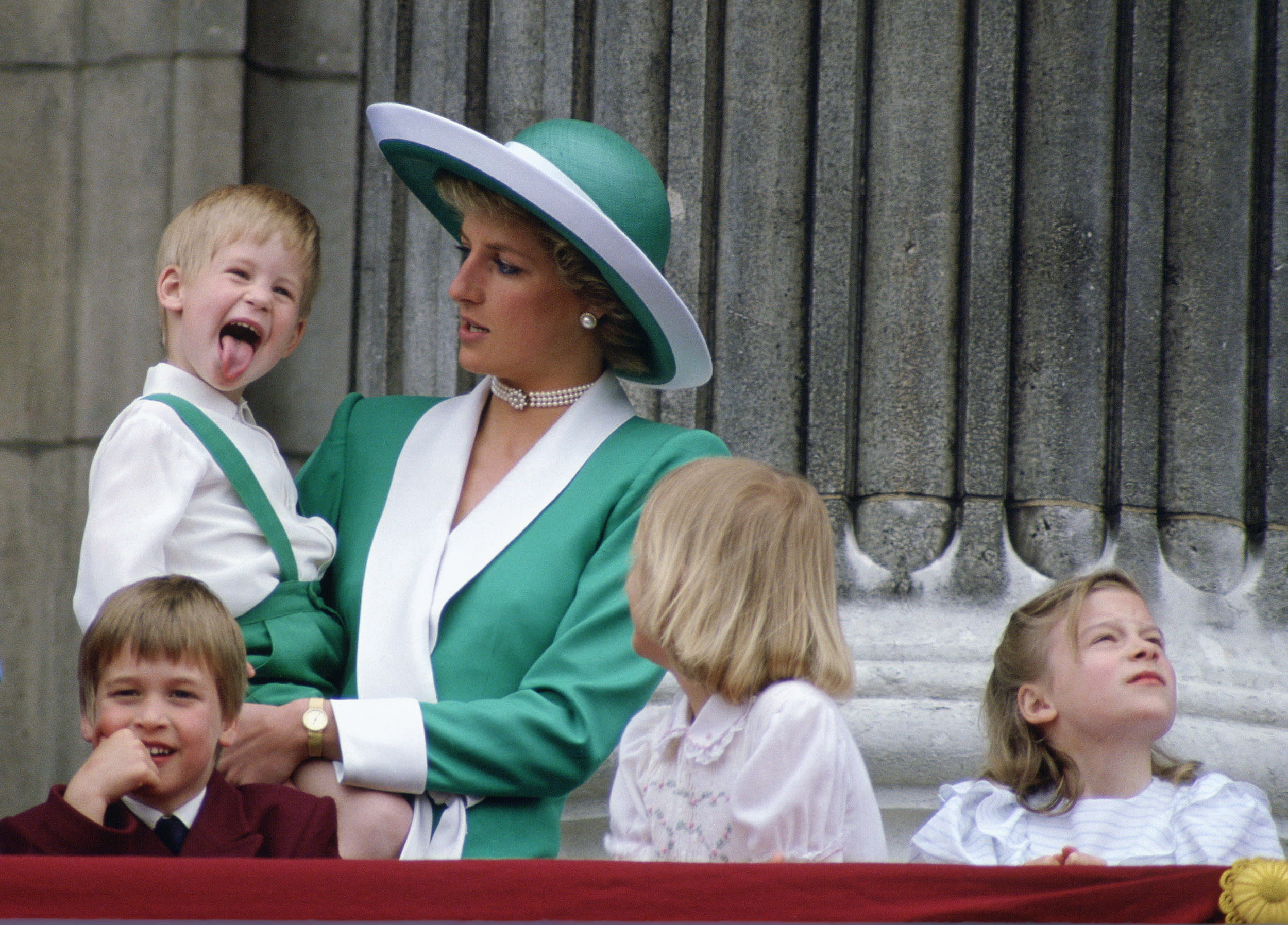 LONDON, UNITED KINGDOM - JUNE 11:  Prince Harry Sticking His Tongue Out Much To The Suprise Of His Mother, Princess Diana At Trooping The Colour With  Prince William, Lady Gabriella Windsor And Lady Rose Windsor Watching From The Balcony Of Buckingham Palace  (Photo by Tim Graham/Getty Images)