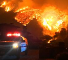 Firefighters defend homes as huge California wildfire rages on
