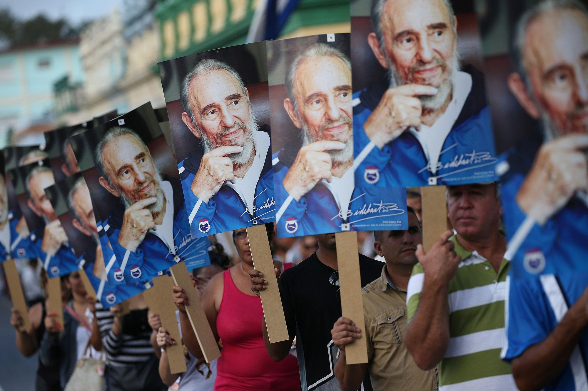 <p>People hold posters while awaitng the arrival of the caravan carrying the ashes of Fidel Castro in Las Tunas, Cuba on Dec. 2, 2016. (Carlos Barria/Reuters) </p>