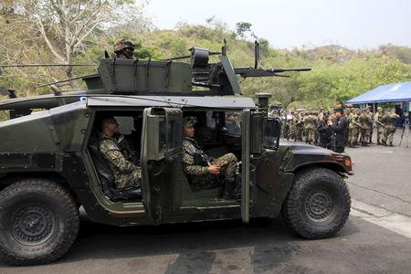 Members of the Territorial Intervention force, a combined army-police unit, participate in a presentation ceremony at La Campanera Neighborhood in Soyapango