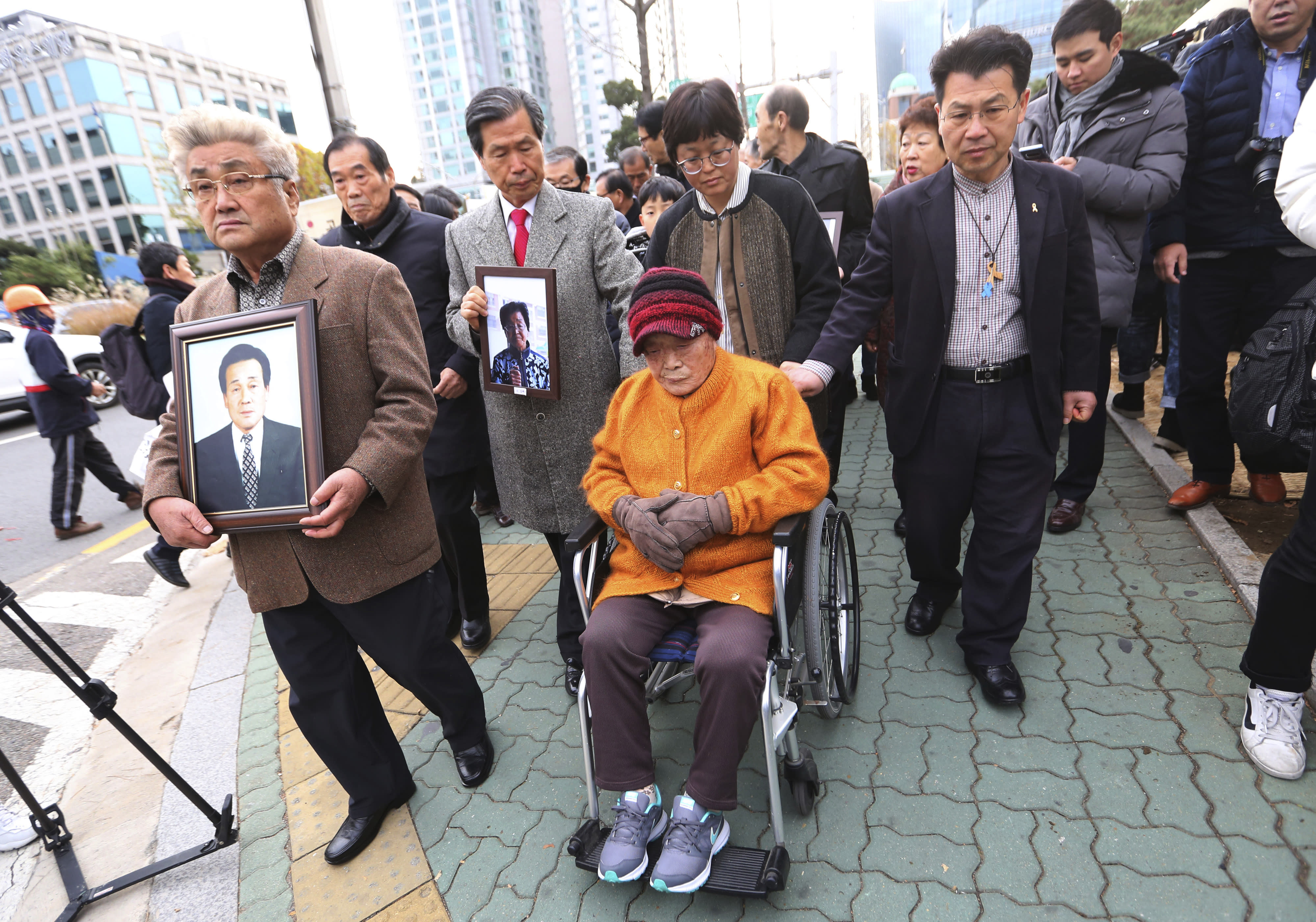 FILE - In this Nov. 29, 2018, file photo, Kim Sung-joo, bottom center, a victim of Japan's forced labor, arrives at the Supreme Court's in Seoul, South Korea. South Korea's top court ordered a Japanese company to compensate 10 Koreans for forced labor during Tokyo's 1910-45 colonial rule of the Korean Peninsula. The modern legacy of a dark chapter in Japan's history, when hundreds of thousands of people were brought from the Korean Peninsula and other Asian nations to work in logging, in mines, on farms and in factories as forced labor, lives on in the companies that came to dominate the Japanese economy after World War II. Many of those companies are still facing demands for compensation that they say were settled by treaty decades ago. (AP Photo/Ahn Young-joon, File)