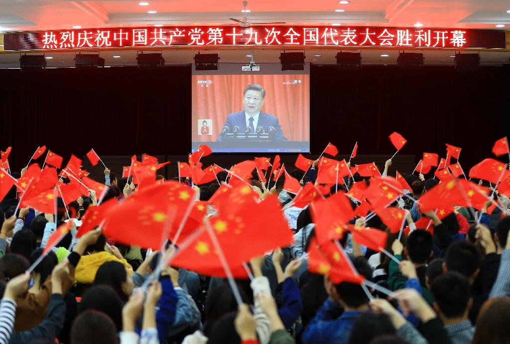 College students waving national flags as they watch the opening of the Communist Party Congress in Huaibei in China's east (AFP Photo/STR)