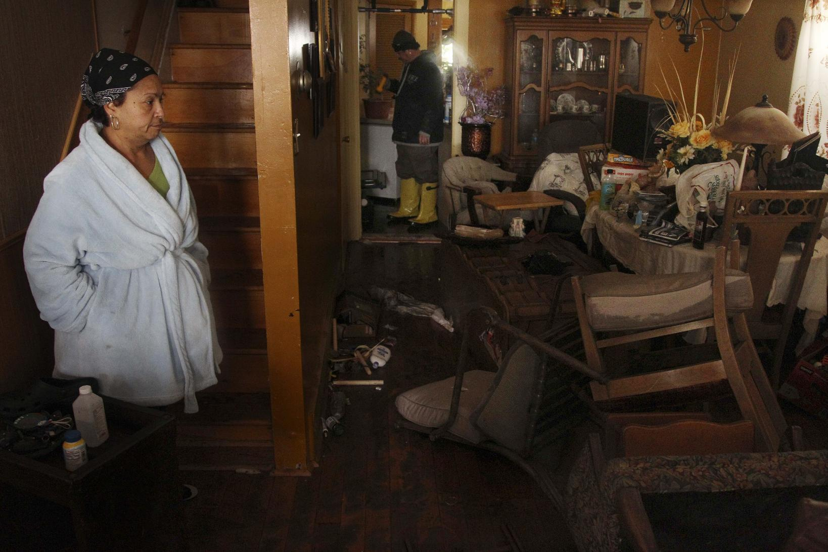 Virgen Perez, left, and her husband Nelson Rodriguez, center, look around their home which was flooded by Storm Sandy in Atlantic City, N.J. on Tuesday, Oct. 30, 2012. Their family stayed on the second floor of their home during the storm. (AP Photo/Seth Wenig)