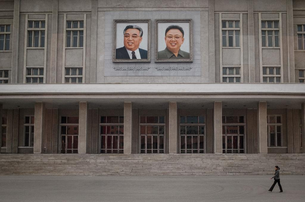 A woman walks before portraits of late North Korean leaders Kim Il-Sung and Kim Jong-Il on the facade of a building in Pyongyang on October 8, 2015 (AFP Photo/Ed Jones)