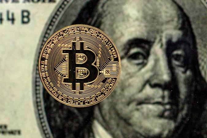 SPAIN - 2021/05/04: In this Photo illustration, a Bitcoin is seen against a background of a one hundred dollars bill. (Photo Illustration by Thiago Prudencio/SOPA Images/LightRocket via Getty Images)