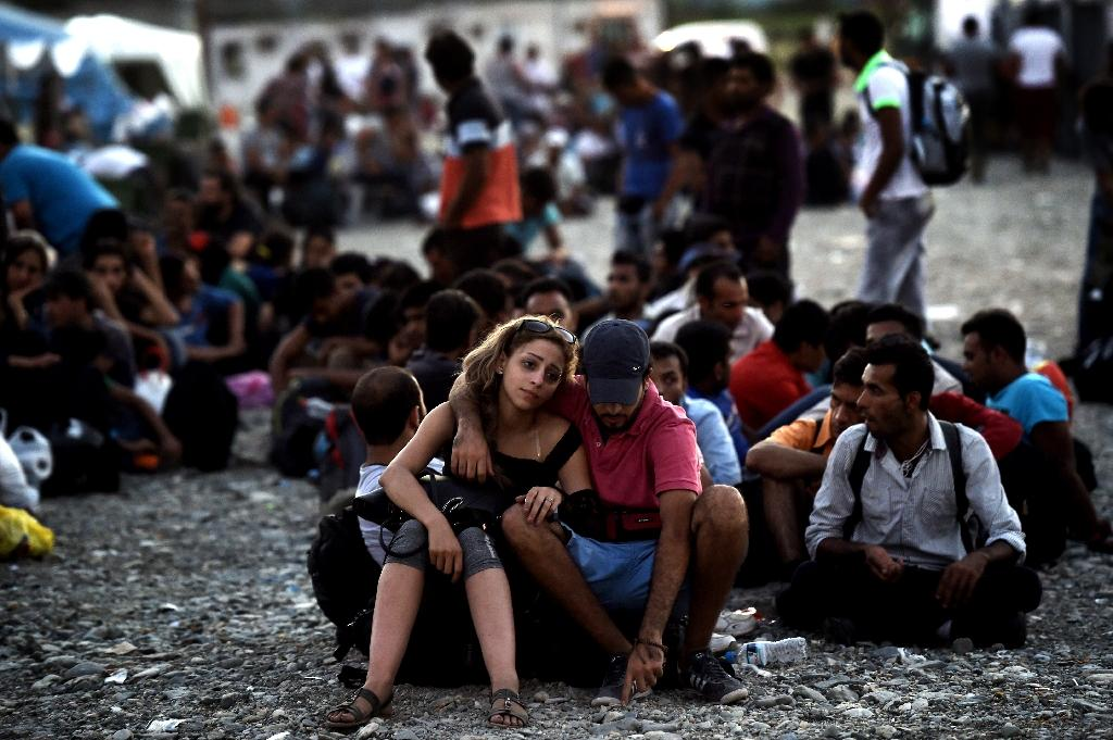 A Syrian couple waits with other migrants for the train near a train station at the F.Y.R. of Macedonia's village of Gevgelija on August 29, 2015 (AFP Photo/Aris Messinis)