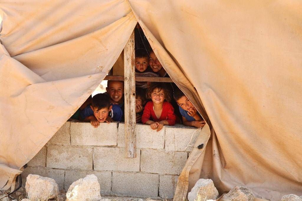 Palestinian children look out from a window in the Palestinian village of Khirbet Zanuta, located in the hills south of the West Bank city of Hebron (AFP Photo/Hazem Bader)