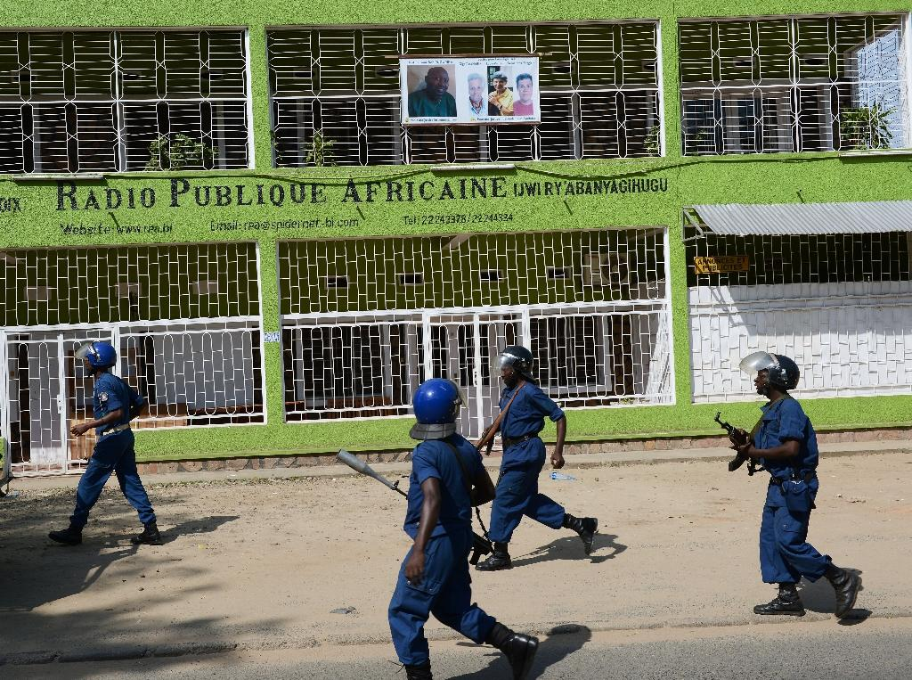 Burundian riot police pass the offices of independent radio station African Public Radio (RPA) in Bujumbura on April 29, 2015 after the authorities shut it down (AFP Photo/Simon Maina)