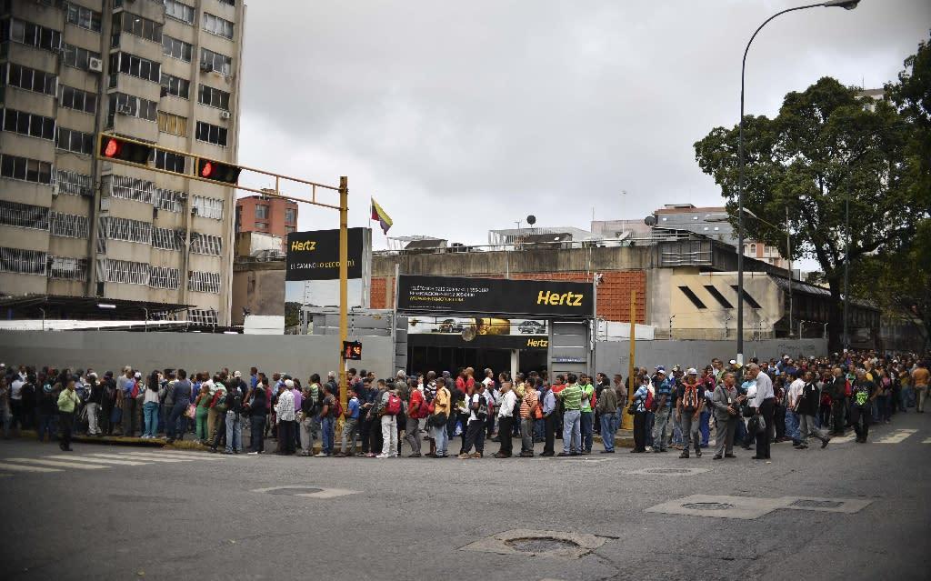 People wait in line to board a bus in Caracas, Venezuela on March 14, 2019 (AFP Photo/YURI CORTEZ)