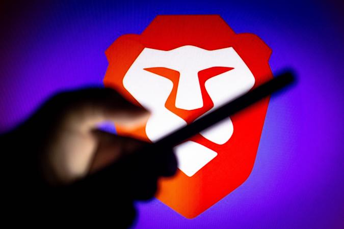 BRAZIL - 2021/01/20: In this photo illustration, a hand of a person holds a smartphone with a Brave Browser logo displayed in the background. (Photo Illustration by Rafael Henrique/SOPA Images/LightRocket via Getty Images)