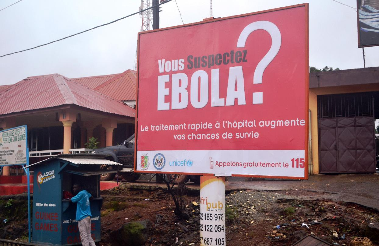 A man stands at a stall on September 8, 2014 next to a billboard about the Ebola virus in a street in Conakry