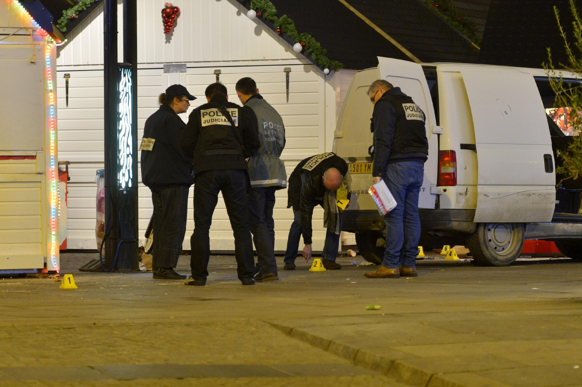 Police inspect the van a driver used to plough into a Christmas market, injuring at least 10 people before stabbing himself in the western French city of Nantes on December 22, 2014 (AFP Photo/Georges Gobet)